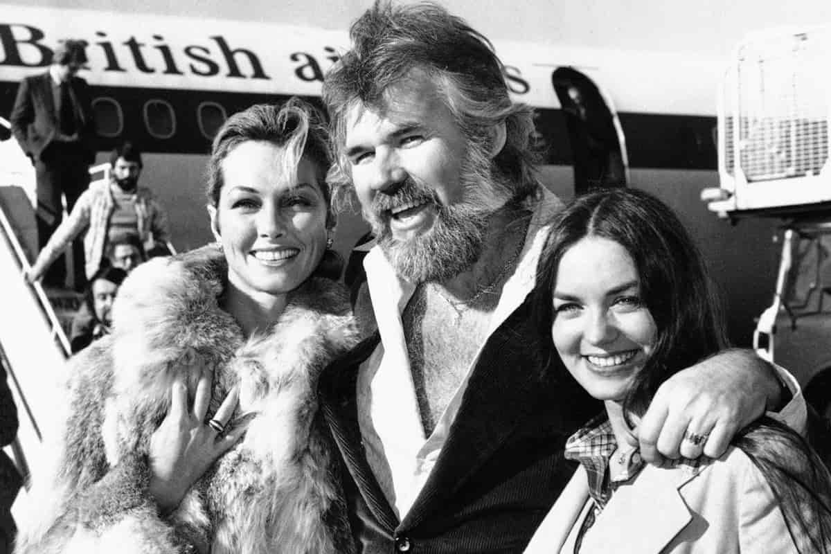 Kenny Rogers llega al aeropuerto londinense de Heathrow con sus dos damas favoritas