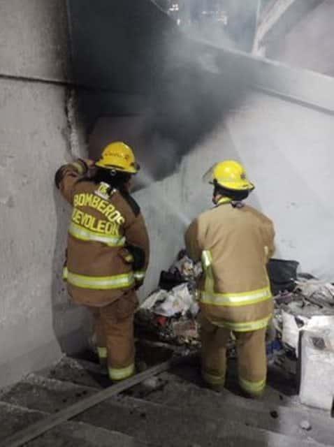 Indigentes prenden fuego a un montón de basura bajo un puente vehicular